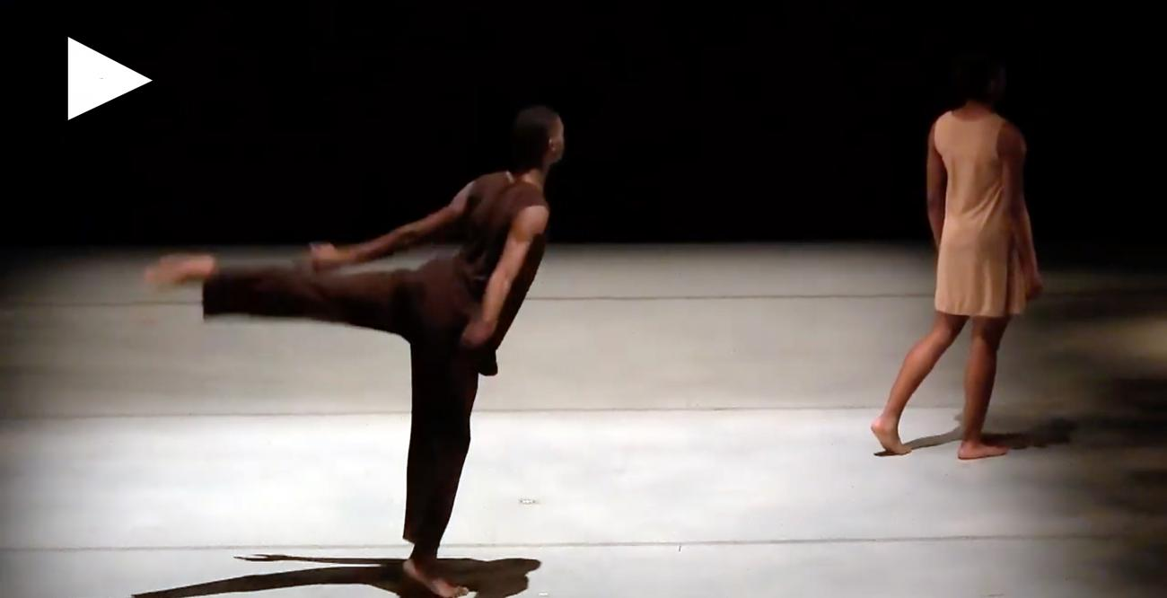 Two dancers on stage, one with extended leg