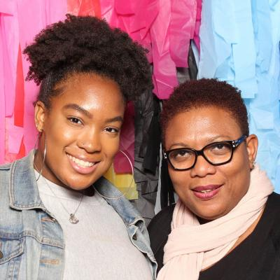 UArts student and parent smile in front of an artist backdrop
